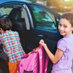 Niños subiendo a un auto negro